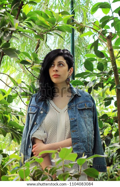 Woman with black hair standing in the middle of a garden.