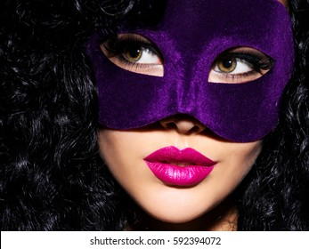 woman with black hairs and violet mask on face.