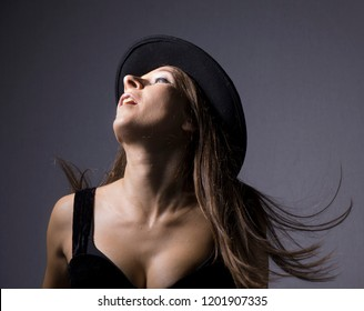 A woman with black hat and decolletage posing in front of the grey background