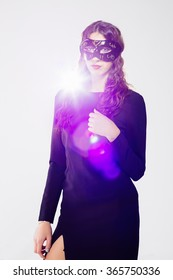 Woman in black hold mask on his face. Contr-studio light hotspot.