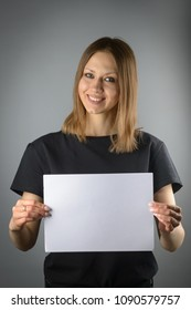 A woman in black holds an empty white sheet of paper