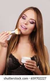 Woman in black lace lingerie applying anti-shine loose powder with brush to her face. Pretty gorgeous girl beautifying. Fashion and makeup