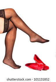 Woman with black, lace stockings and red shoes in front of her tired feet