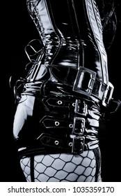 woman in black latex uniform - corset with metal buckles