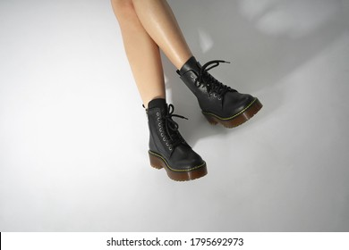 woman in black leather shoes from the new collection on a white background girl's legs in fashionable eco-leather shoes fall-winter 2020. macro photo