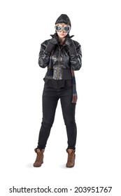 A woman in black leather, stands with aviator leather hat, scarf and goggles on a white backdrop.