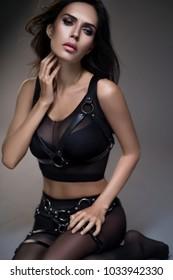 Woman in black lingerie sitting on floor