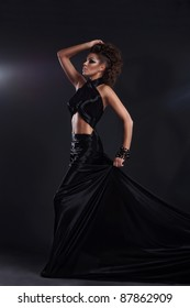 Woman in black long dress over dark background