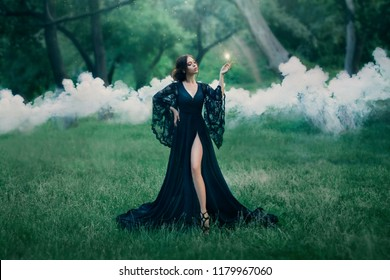 woman in a black long dress with a trailer and lace sleeves. magic. witchcraft. leg, slender figure.stealing soul, spirit hunter, fire in hands, sparks, mysteries, smoke, forest, art photo. sun light.