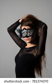 Woman in black mask and dress and lond hair studio portrait
