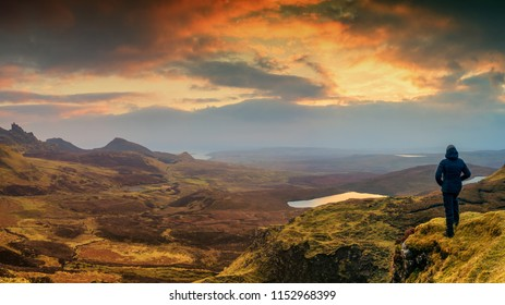 A woman in a black outdoor outfit looks at the sunrise on a cliff. Beautiful scenery. Scotland, Isle Of Skye, Quiraing.