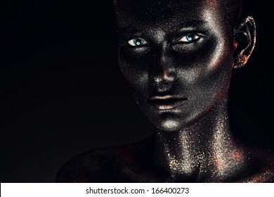 woman in black paint body art with silver glitter