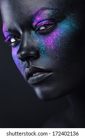 woman in black paint and colourful powder