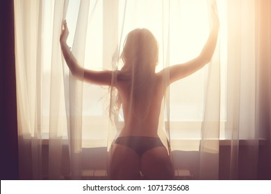 woman in black pants and naked back hiding in tulle of gorgeous elegant lady glamor girl with excellent fitness buttocks having fun happy standing back to camera on window light copy
