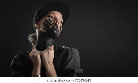 woman in black shirt and hat with black trace of hand on face