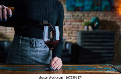 Woman in black shirt and black skirt pouring red wine into wine glass. Close up image of woman holding wine glass, pouring red wine.