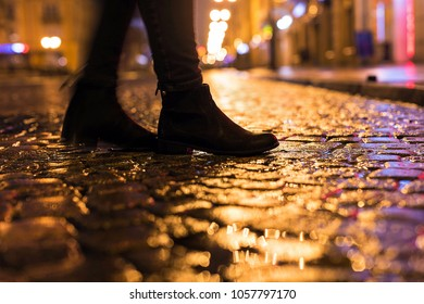 Woman in black shoes walking through the city street