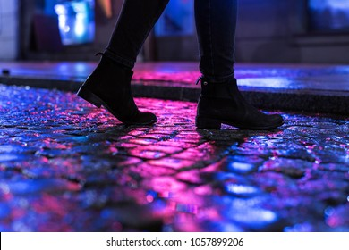 Woman in black shoes walking through the city street in the night