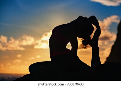 Woman black silhouette on sunset sky background. Young active girl sit in yoga pose on beach rock, stretching to keep fit. Healthy lifestyle, outdoor fitness, sports activity on summer family holiday.
