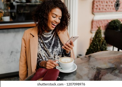 Woman with black skin and candid smile chatting by  phone and enjoying  coffee break in cafe . Wearing elegant velvet dress and beige coat.