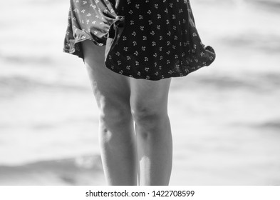 Woman in black skirt in the windy weather on beach. Goosebumps on legs skin. Black and white processing