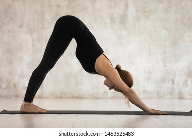Woman in black sportswear do Downward-Facing Dog Adho Mukha Svanasana yoga pose. Deeply stretches back, stimulates brain, improves memory, energizes of muscles, active healthy lifestyle hobby concept