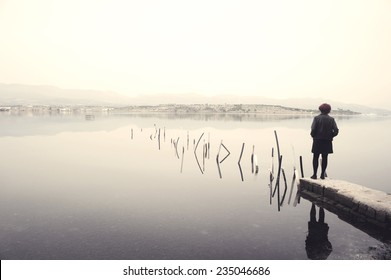 Woman in black standing on jetty in a lake looking at the scenery. Edited image with vintage effect