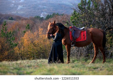 Woman in black stands next to a horse on nature