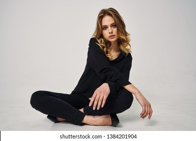 woman in a black suit sitting in the lotus position on the floor fashion