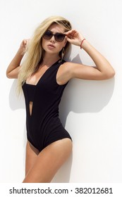 Woman in black sunglasses and swimsuit poses on white isolated background. Phuket, Thailand