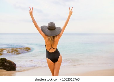 Woman in black swimsuit and summer hat on the beach