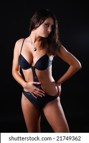woman in black swimwear standing on the black background