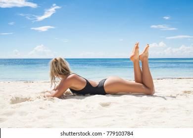 Woman in black swimwear tanning on the beach.