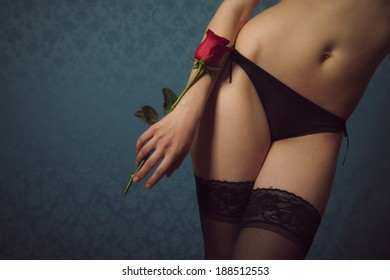 Woman in black underwear, holding a red rose