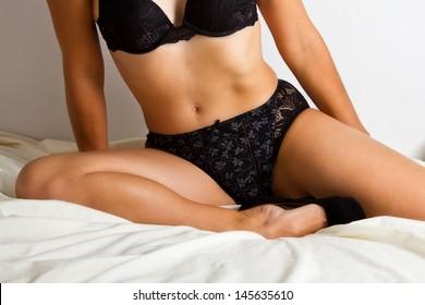 Woman in black underwear lay on bed in studio