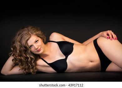 Woman in black underwear laying on the floor