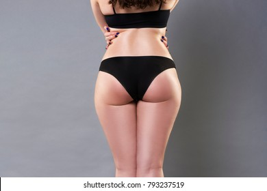Woman in black underwear on gray background, cellulite on female buttocks, skin care concept