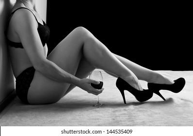 Woman in black underwear sit on floor shoes