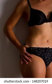 Woman in black underwear stand posing body flat tummy