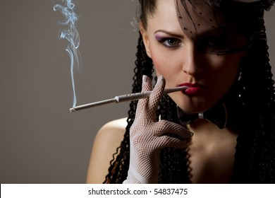 Woman in black veil with a cigarette holder