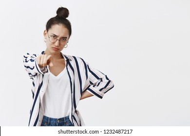 Woman blaming friend, accusing him in crime. Portrait of moody displeased attractive female model in shirt and glasses, pointing at camera, holding hand on hip and frowning from disappointment
