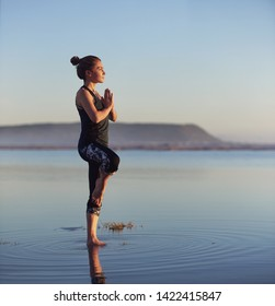 Woman blancing in yoga pose at the beach for a healthy lifestyle