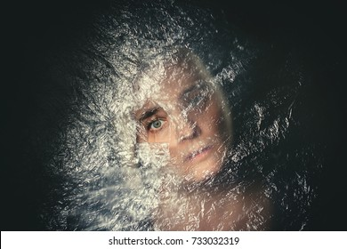 Woman with blank, terrified expression peeking through hole in plastic curtain, scared in dark