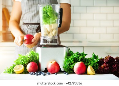Woman blending lettuce leaves, spinach, aplles, berries, bananas. Homemade healthy green smoothie. White kitchen design. Sunny morning with sunlight. Toned effect
