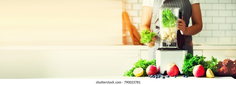 Woman blending lettuce leaves, spinach, aplles, berries, bananas. Homemade healthy green smoothie. White kitchen design. Sunny morning with sunlight. Toned effect. Banner.