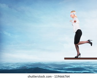 Woman blindfolded walking on a board over the sea