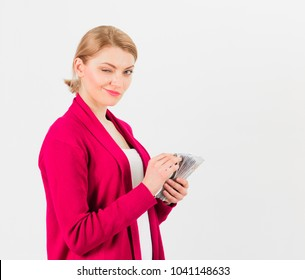 Woman with blinking face counting money, isolated on white background. Business lady holds cash, banknotes in hands, copy space. Business lady concept. Girl in suit earn money, got salary, payday.