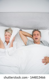 Woman blocking her ears because of partners snoring at home in bed