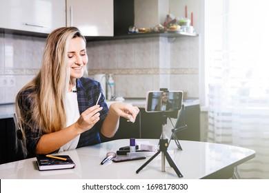 Woman blogger shows foundation on smartphone. Coronavirus quarantine homework, social distance, private entrepreneur. Selected Focus.