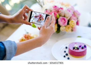 woman blogger smartphone photo party pastries concept. creation process. dependency of social network.